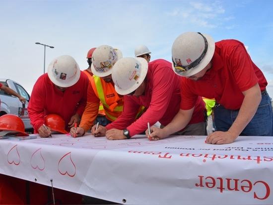Los trabajadores de construcción de las compañías del edificio de McCarthy firman una bandera de la salud del corazón dedicada a los pacientes en el centro médico conmemorativo de Torrance durante ...